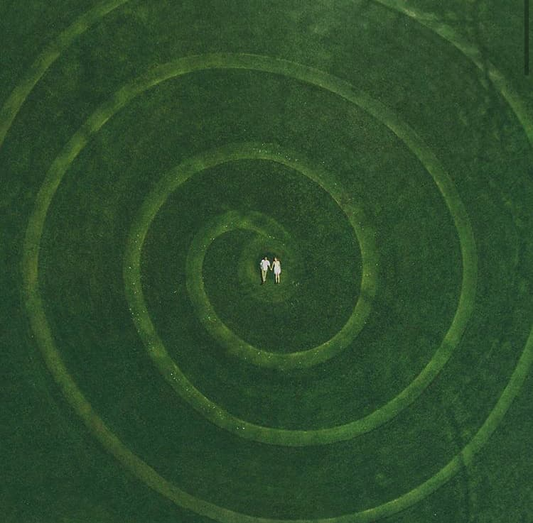 Image of spiral on a green field, with two figures lying in the center.
